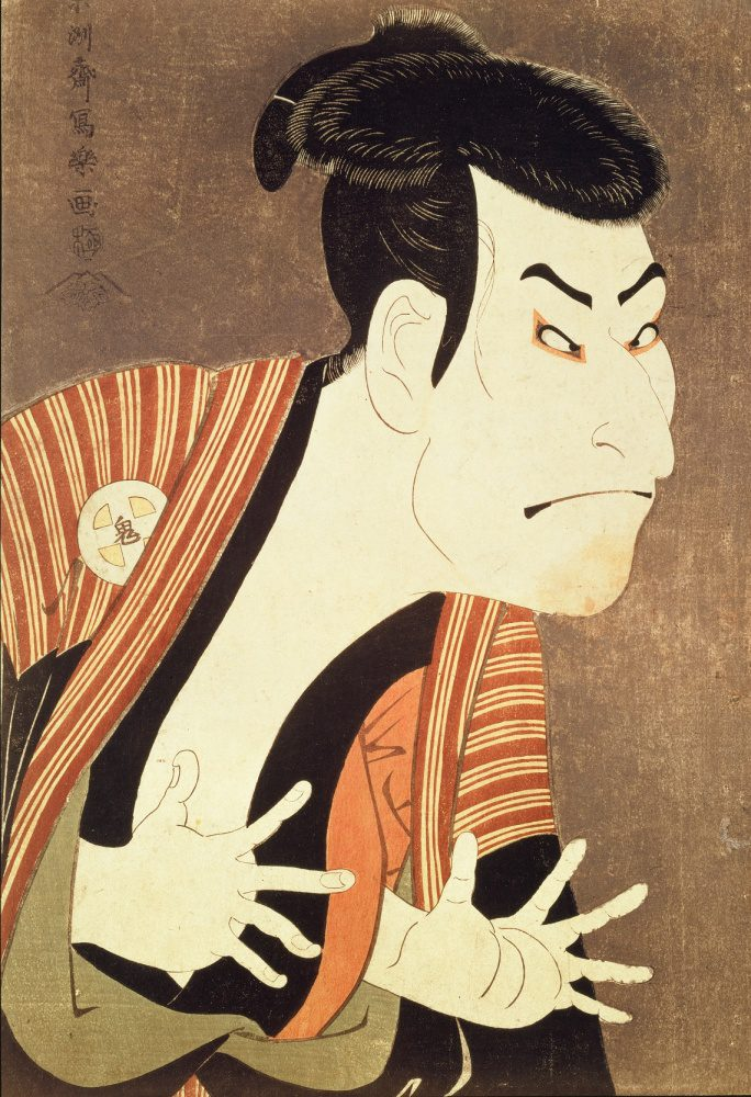 Sharaku creates a colorful portrayal of a kabuki actor. The actor wears a striped robe over his shoulders and gesticulates dramatically with his hands extended in front of him.