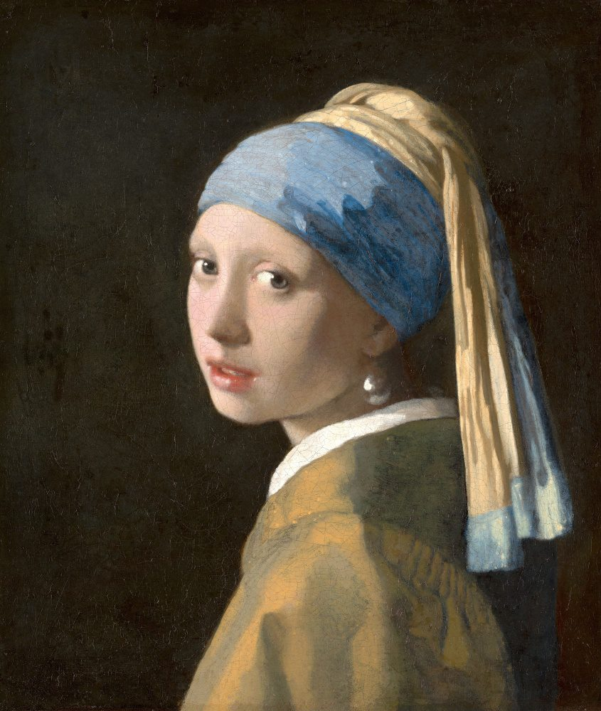 A white woman in three-quarters view, donning a yellow and blue headdress, looks over her left shoulder to exchange gazes with the viewer. Her large pearl earring catches the light.
