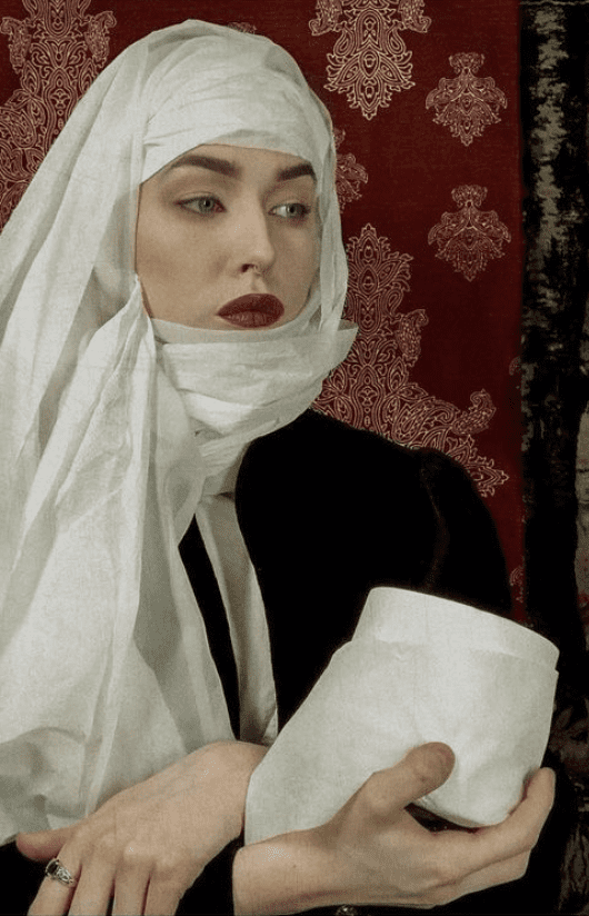A woman in three-quarters view with crossed wrists holds a roll of toilet paper. She wears a toilet paper headdress and make-up to resemble Bernhard Strigel's Portrait of Martha Thannstetter.