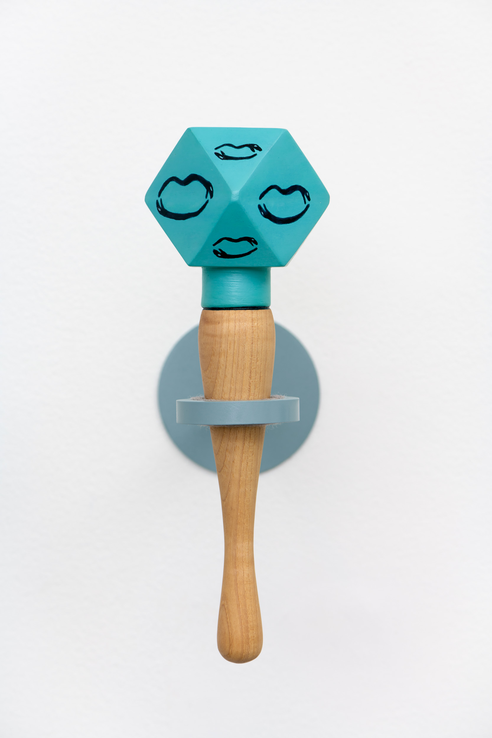 A blue, multifaceted ceramic rattle with a wooden handle. Each facet is decorated with a line drawing of two snakes laid flat in the shape of a mouth.