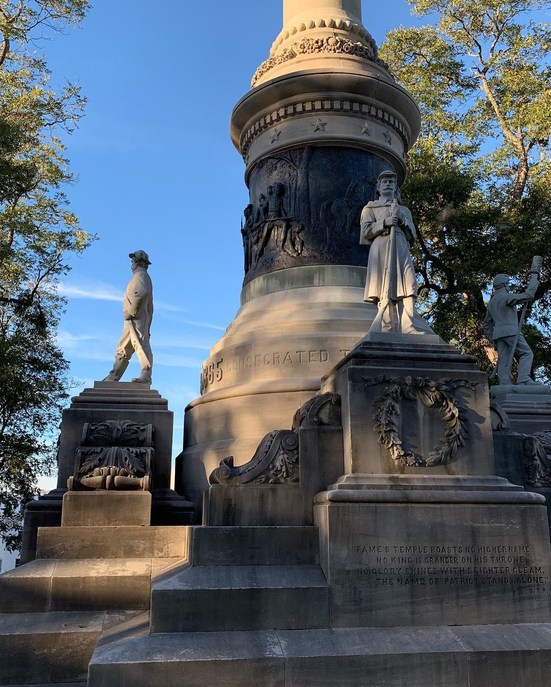 Stone monument to the Civil War with sculptures of soldiers and figures of women signifying victory