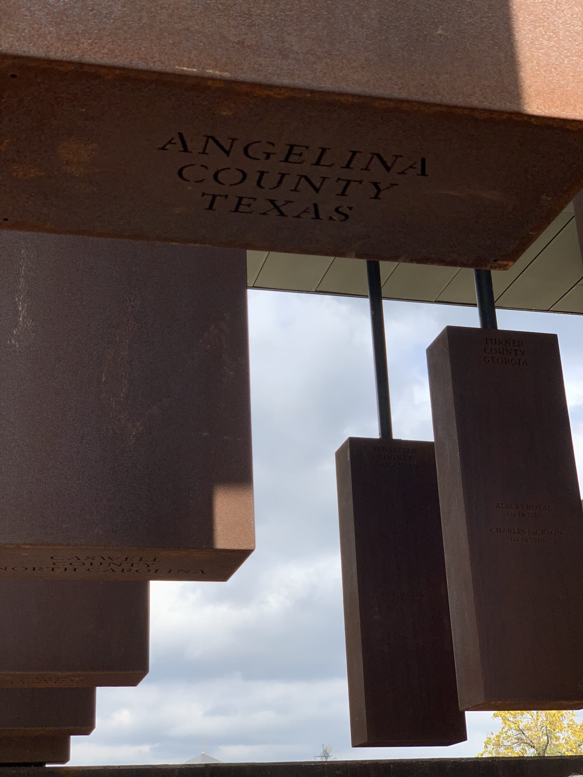 stelae rising above the viewer with partial blue sky