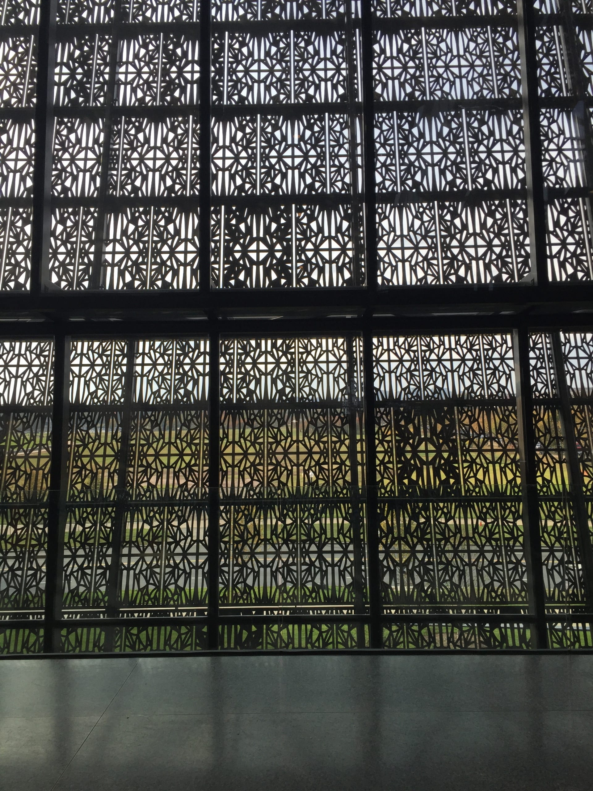 interior of museum showing light coming in through porous metal screens