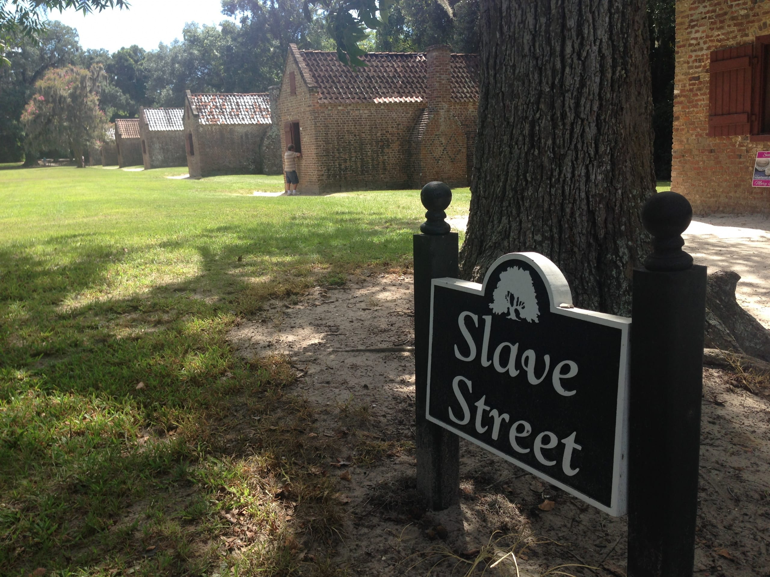 "a sign that reads ""slave stret"" with three cabins in the background"