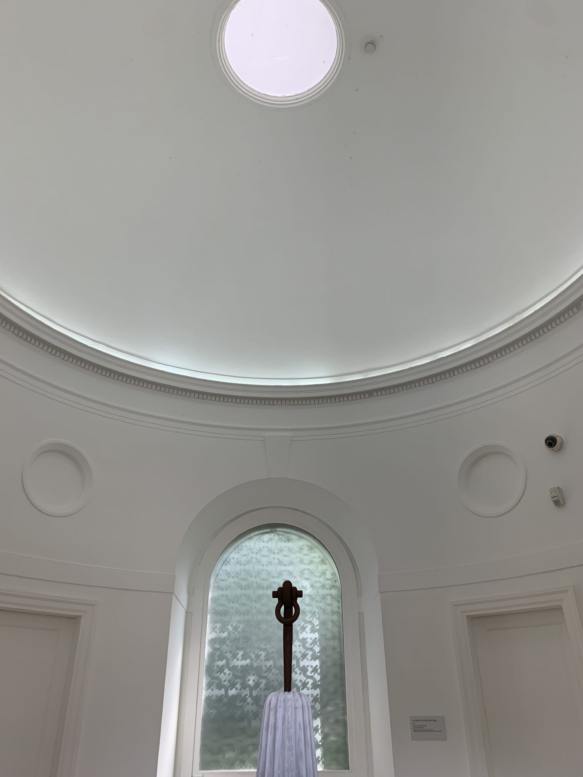 light-filled Neo-Classical rotunda with an oculus. A tapered column from which a single iron shackle rises