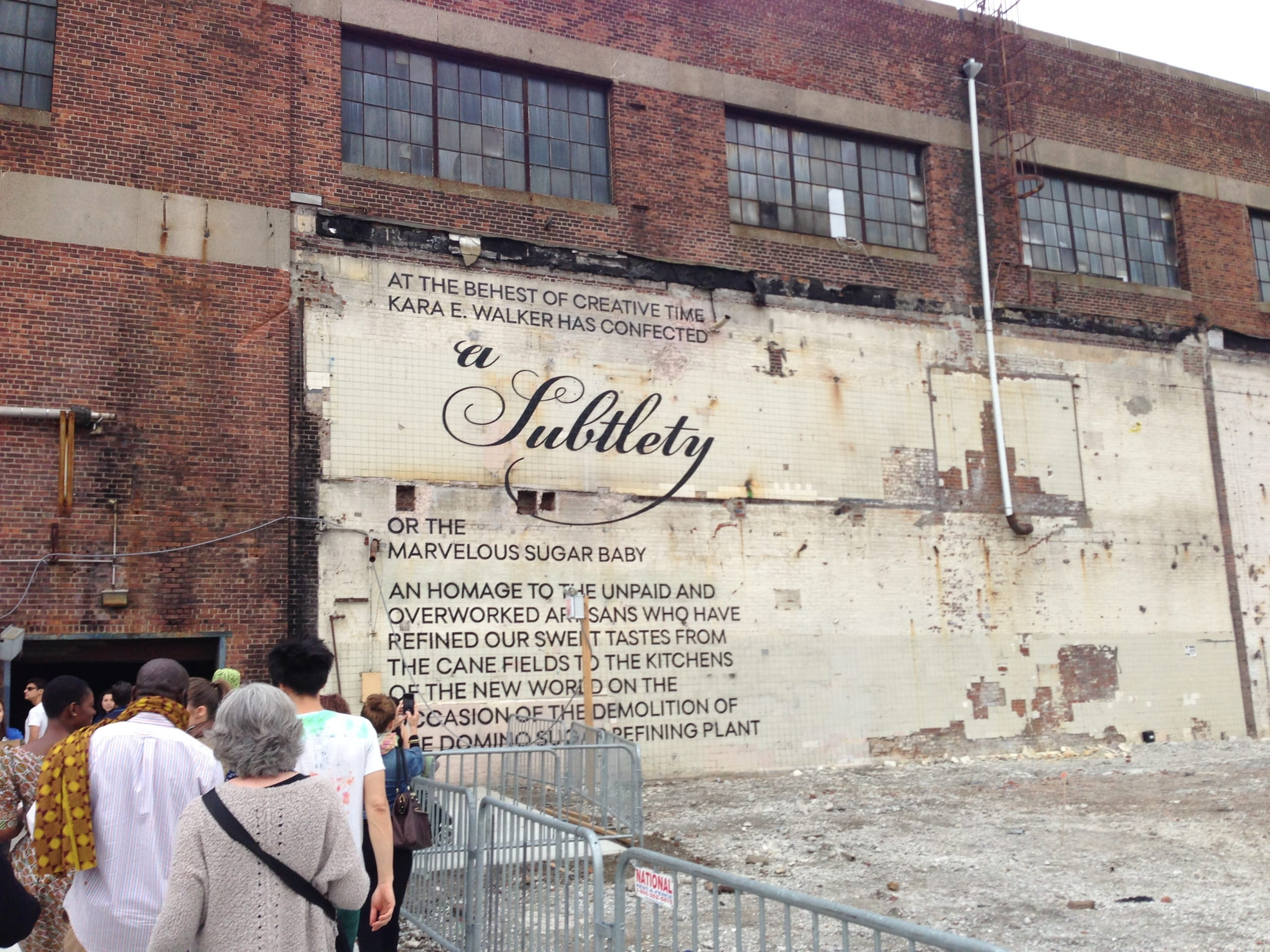 """A Subtlety"" printed onto red brick walls of a factory"
