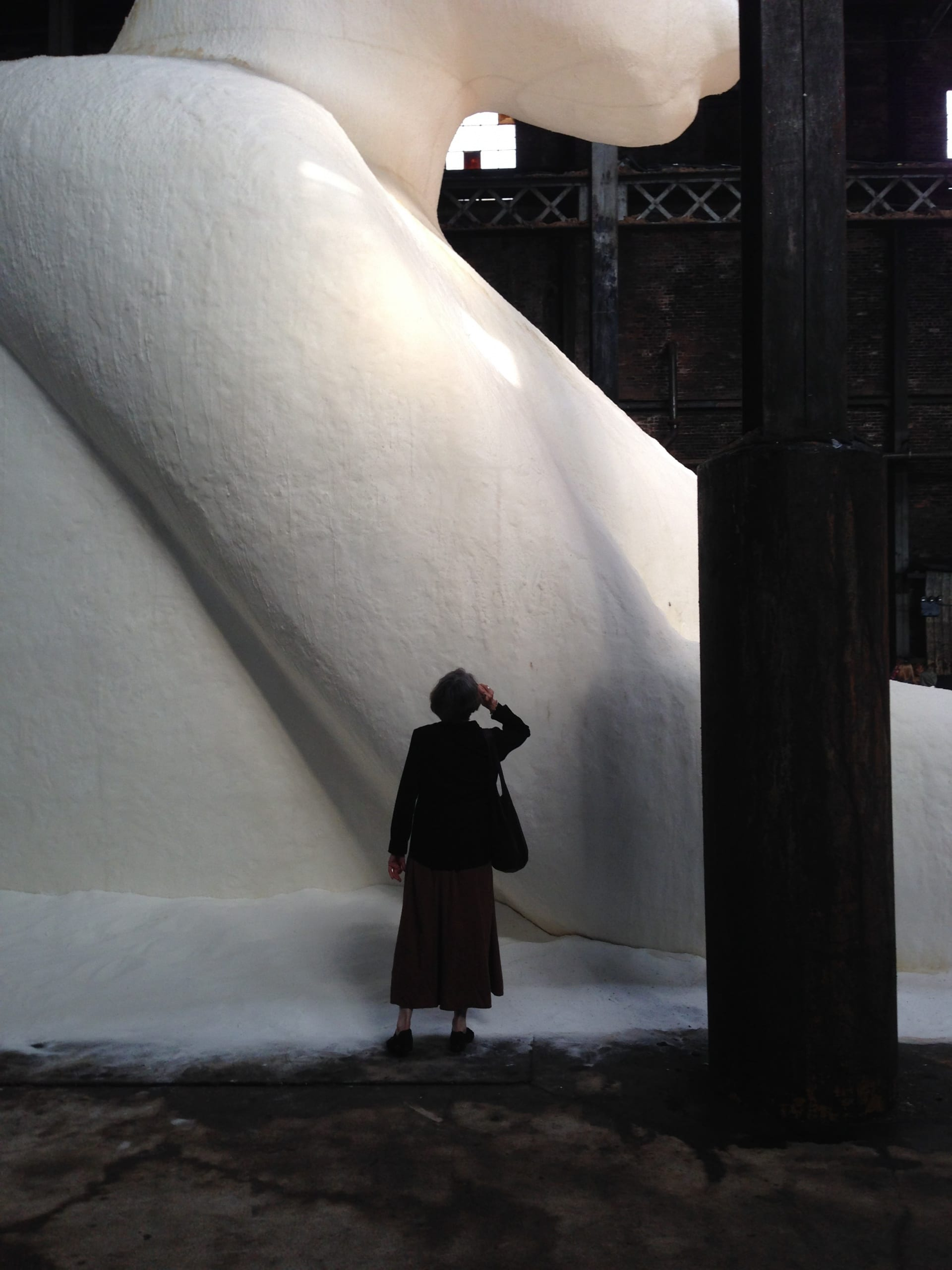 Profile of the sphinx made of cast sugar, with a woman silhouetted in the foreground