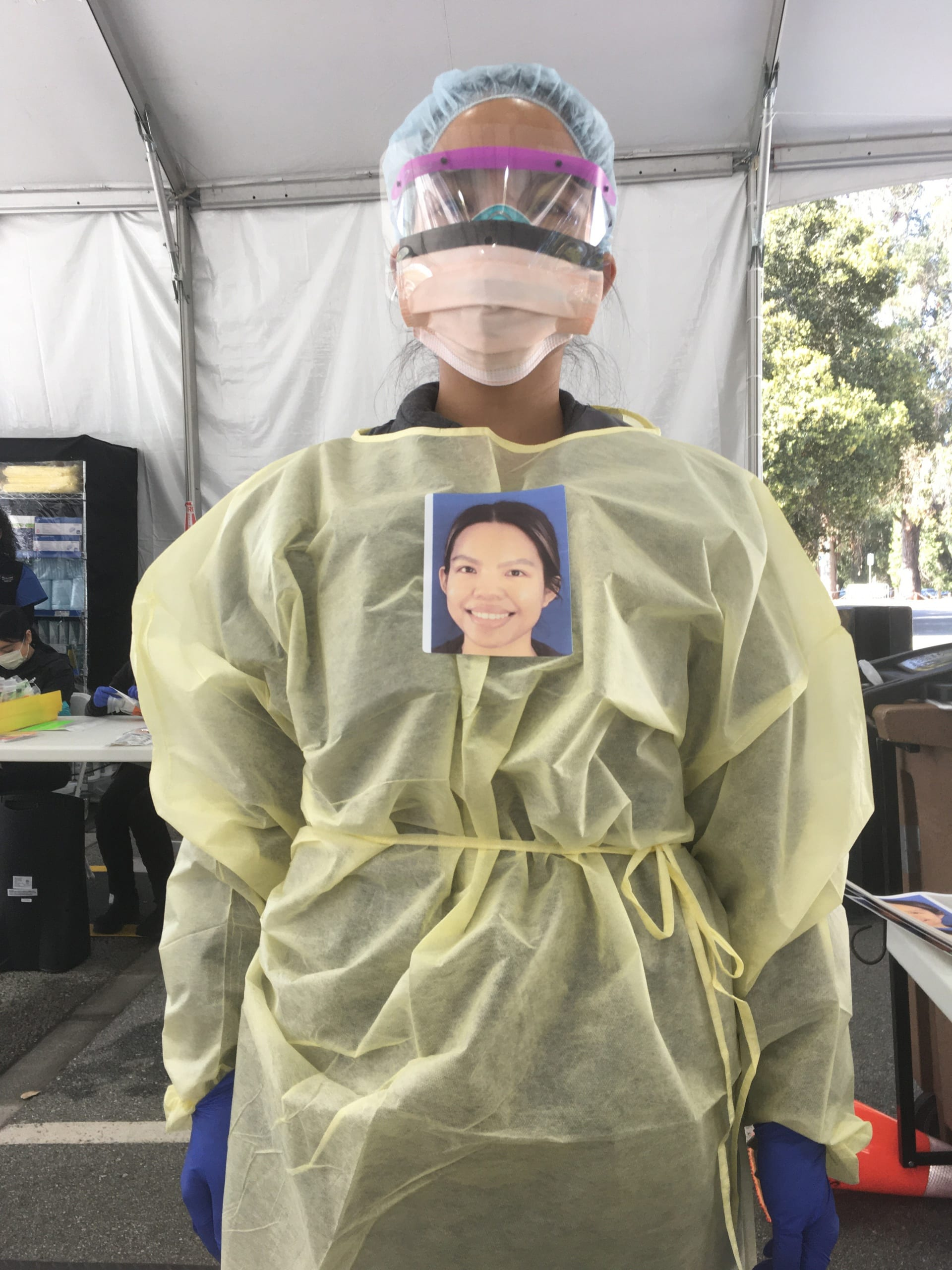 Stanford Express Care nurse Anna Chico, her head and body hidden behind layers of protective gear, wears a smiling portrait affixed over her heart so that people arriving at the COVID-19 testing clinic can see an image of her face