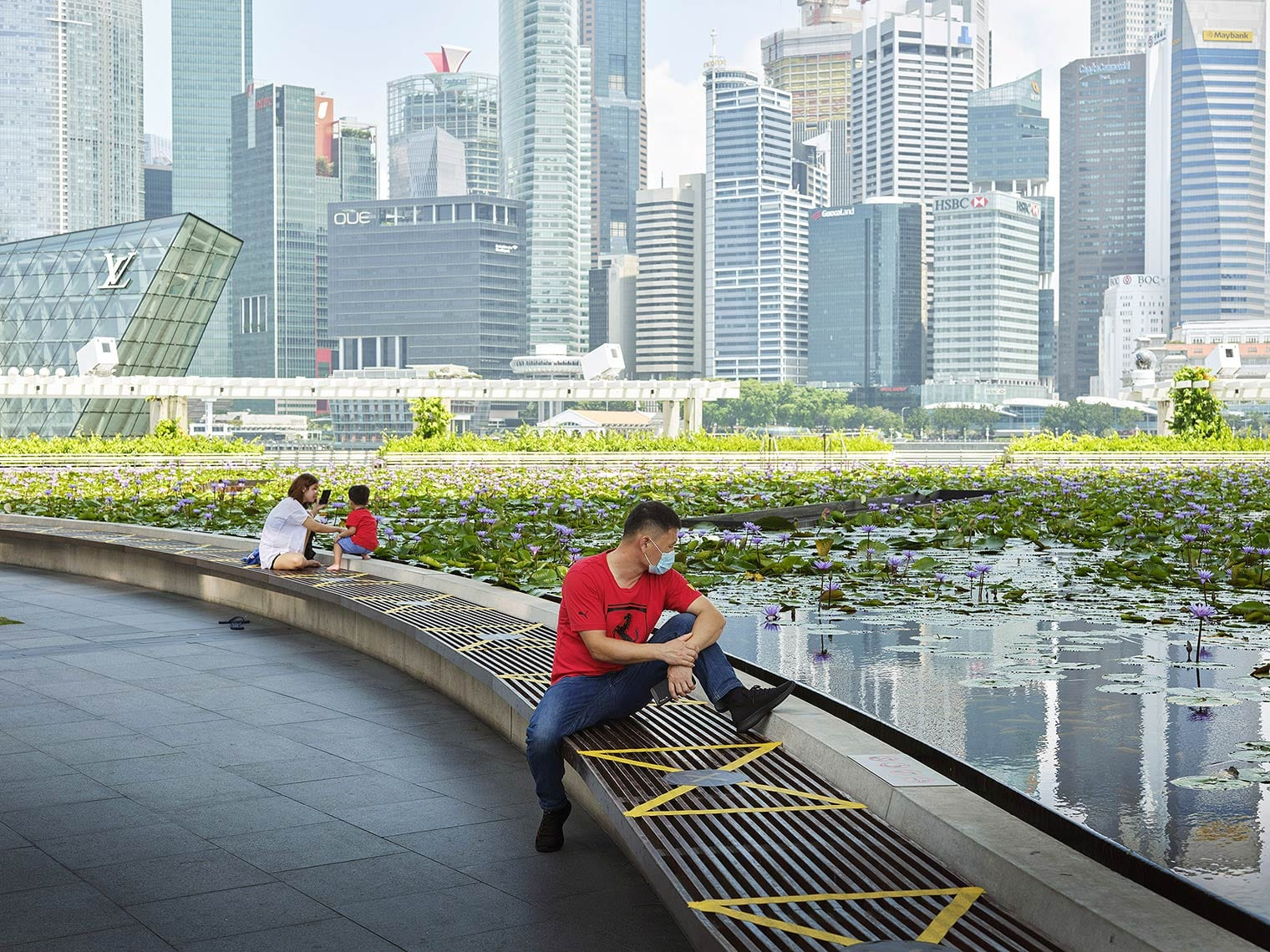 A person wearing a surgical mask sits on a bench by a lily pond in front of Singapore's skyline