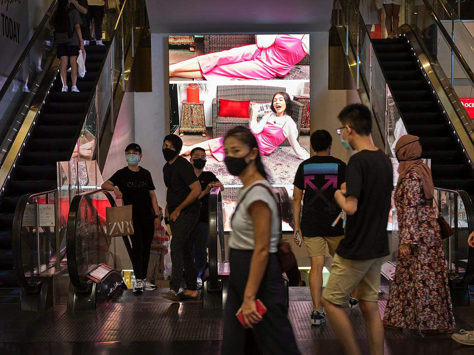 Various mask-wearing shoppers in front of a glowing display at 313@somerset mall in Singapore