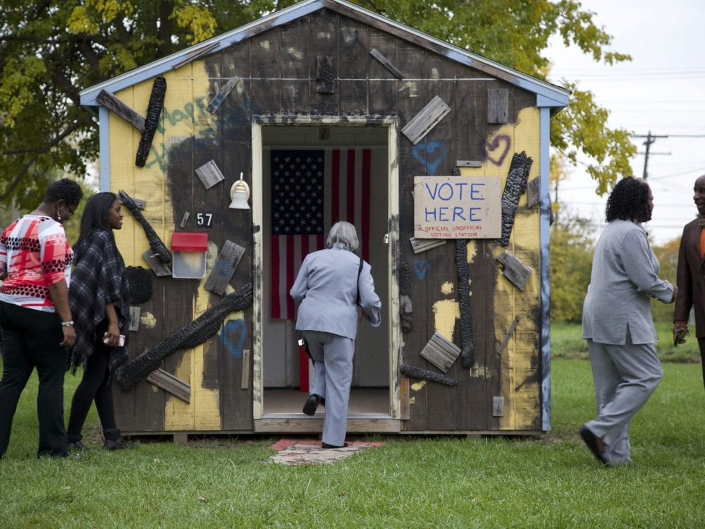 """People standing around a painted wooden structure featuring an American flag and a sign that says """"Vote Here"""""""