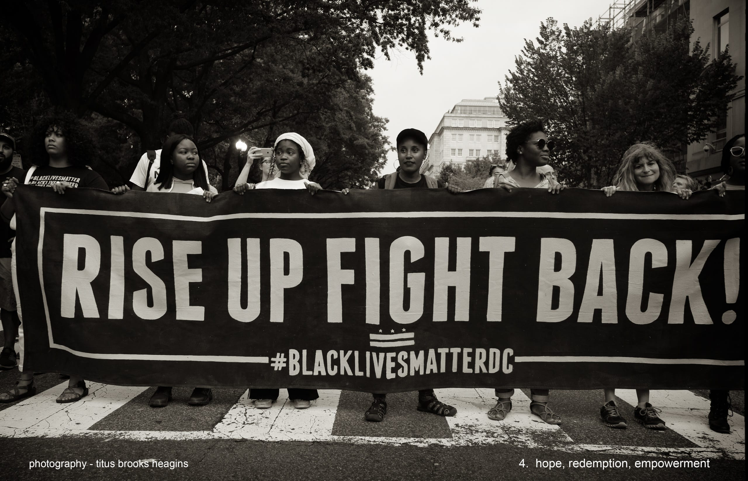 """Black and white photo of a front line of protesters holding a long cloth banner that reads """"Rise Up Fight Back! #BlackLivesMatterDC"""""""