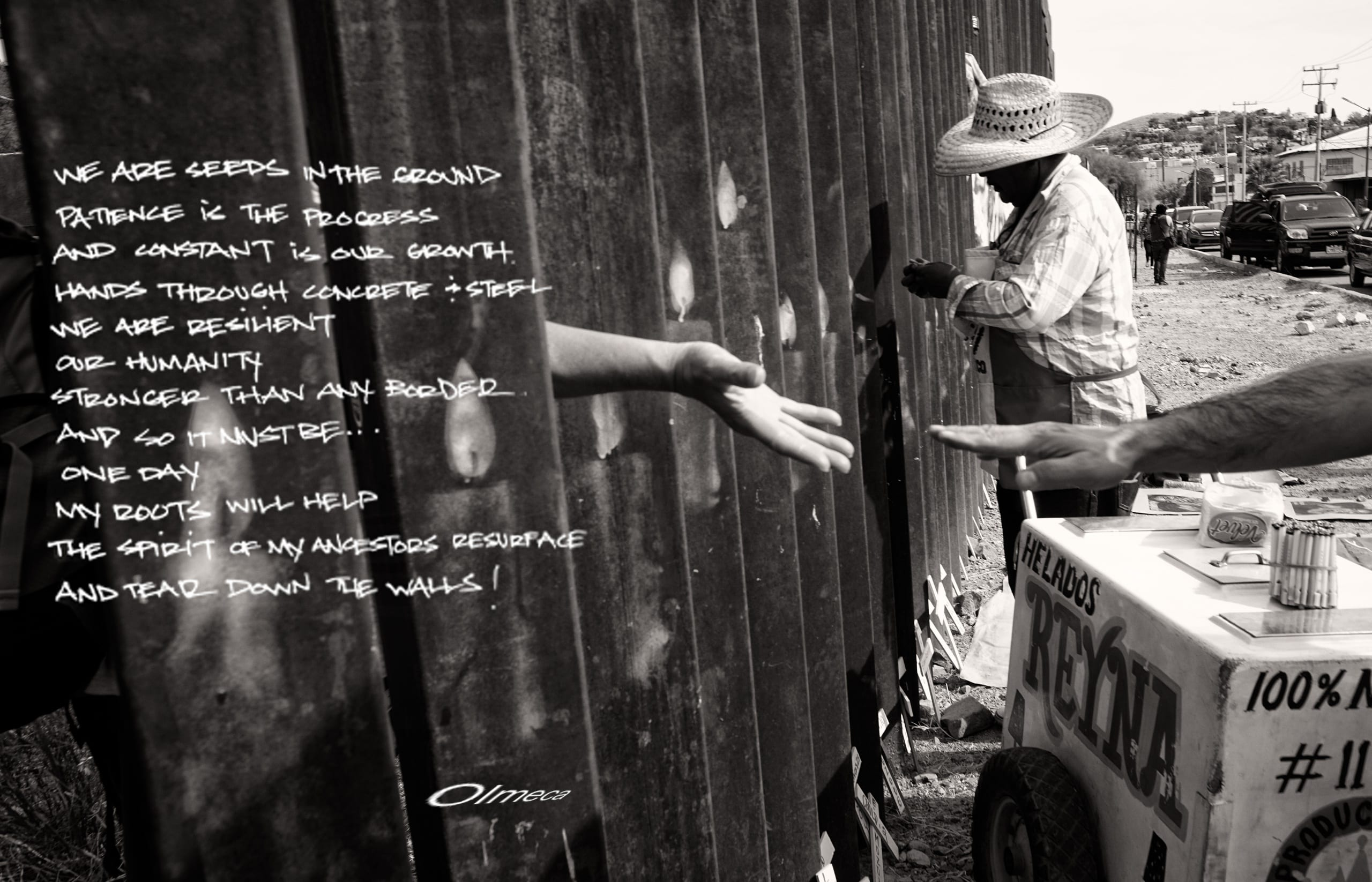 Black and white photo of the US-Mexico border wall built by the United States. A hand strains to reach out through the left-hand side of the image/wall; another hand reaches to meet it from the right-hand side of the border/image. A poem is superimposed over the image's left side.