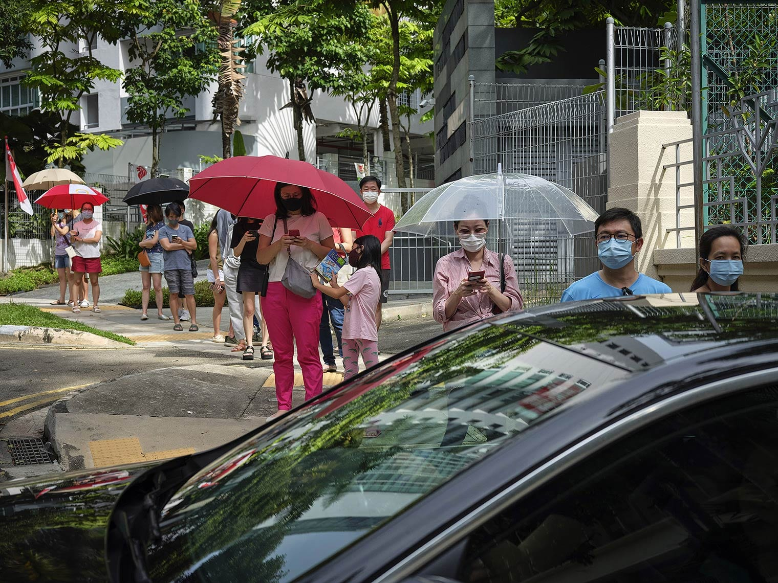 People wearing masks and standing under umbrellas wait in a socially distanced line on a tree-lined city street