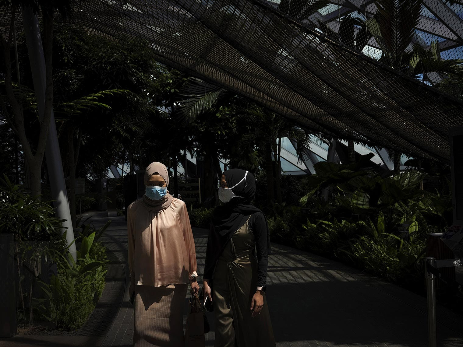 Two masked women walk under a mesh roof, surrounded by greenery