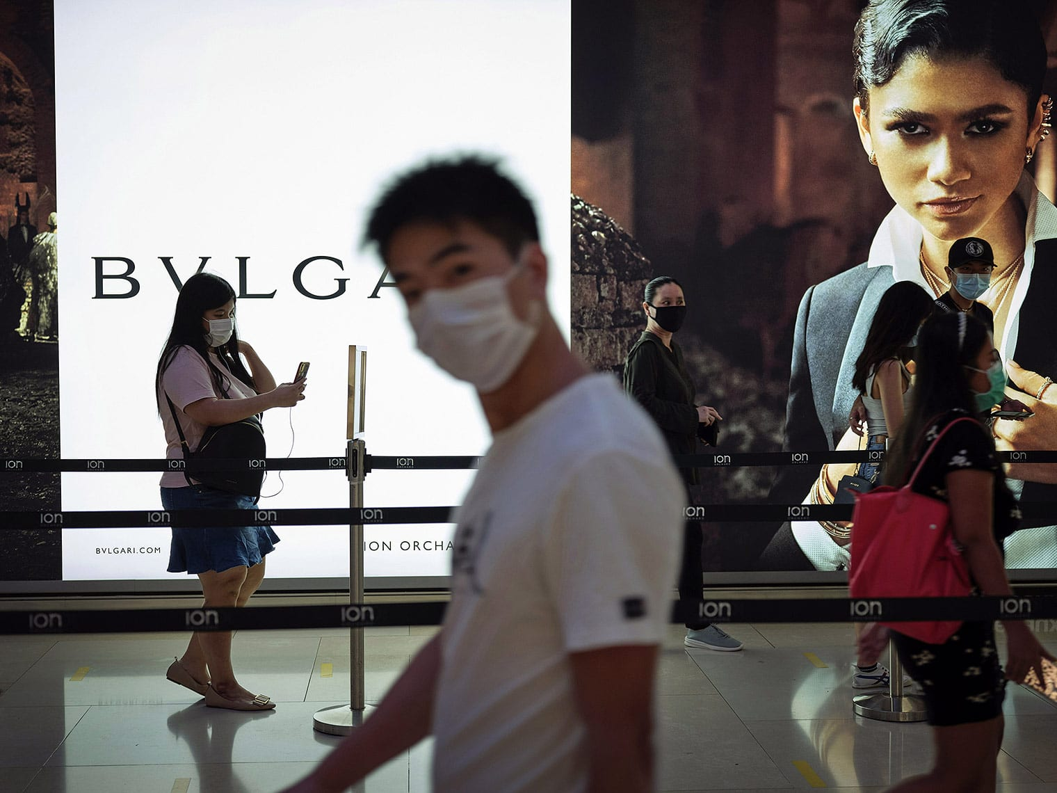 A masked man in the foreground looks at the camera, while shoppers behind him walk in front of backlit ad displays