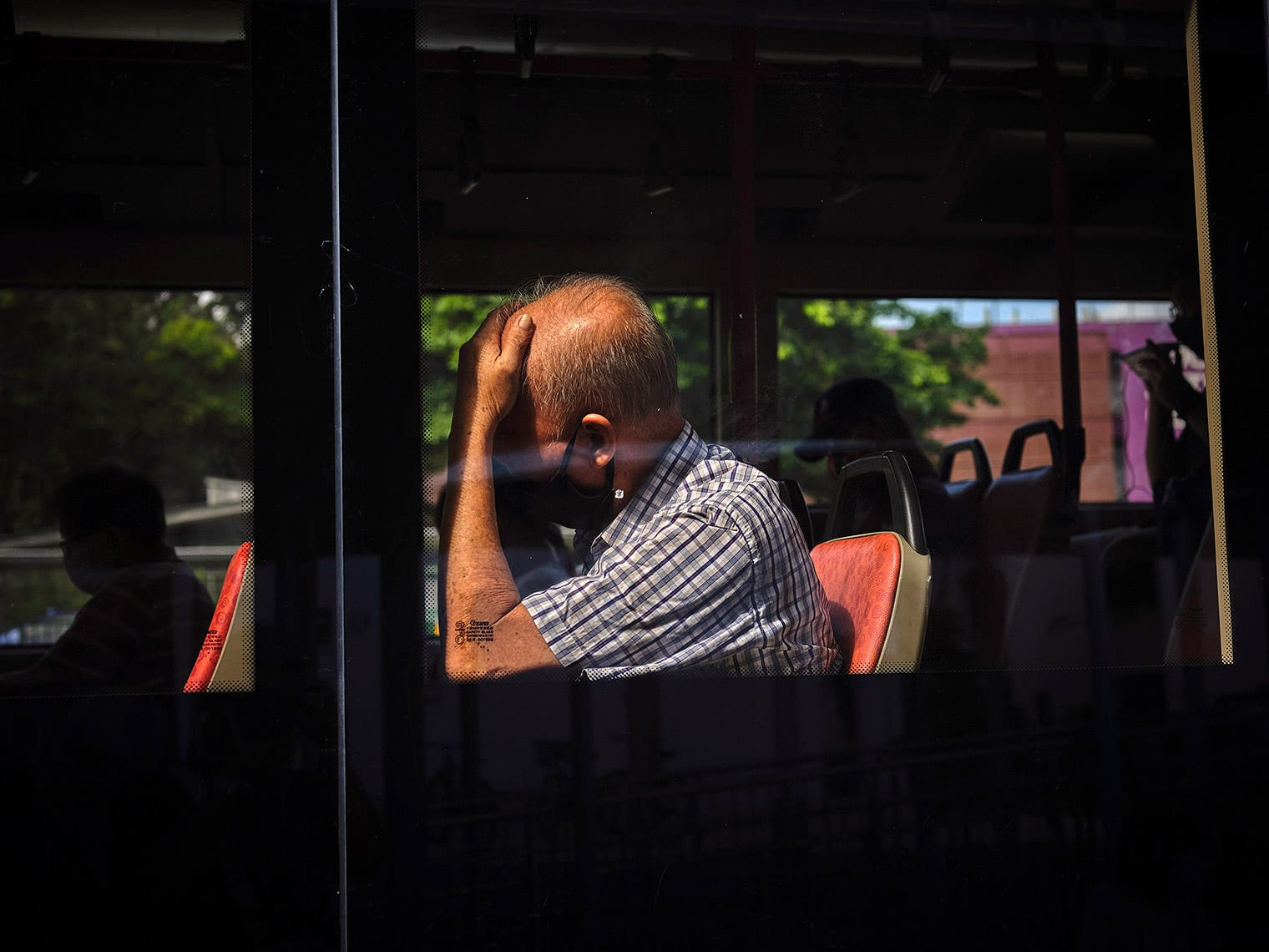 Masked man leans against glass window of a bus, cradling his head
