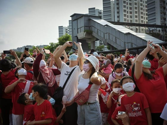 Many masked people wearing red stare at the sky, many with their phones raised to take pictures