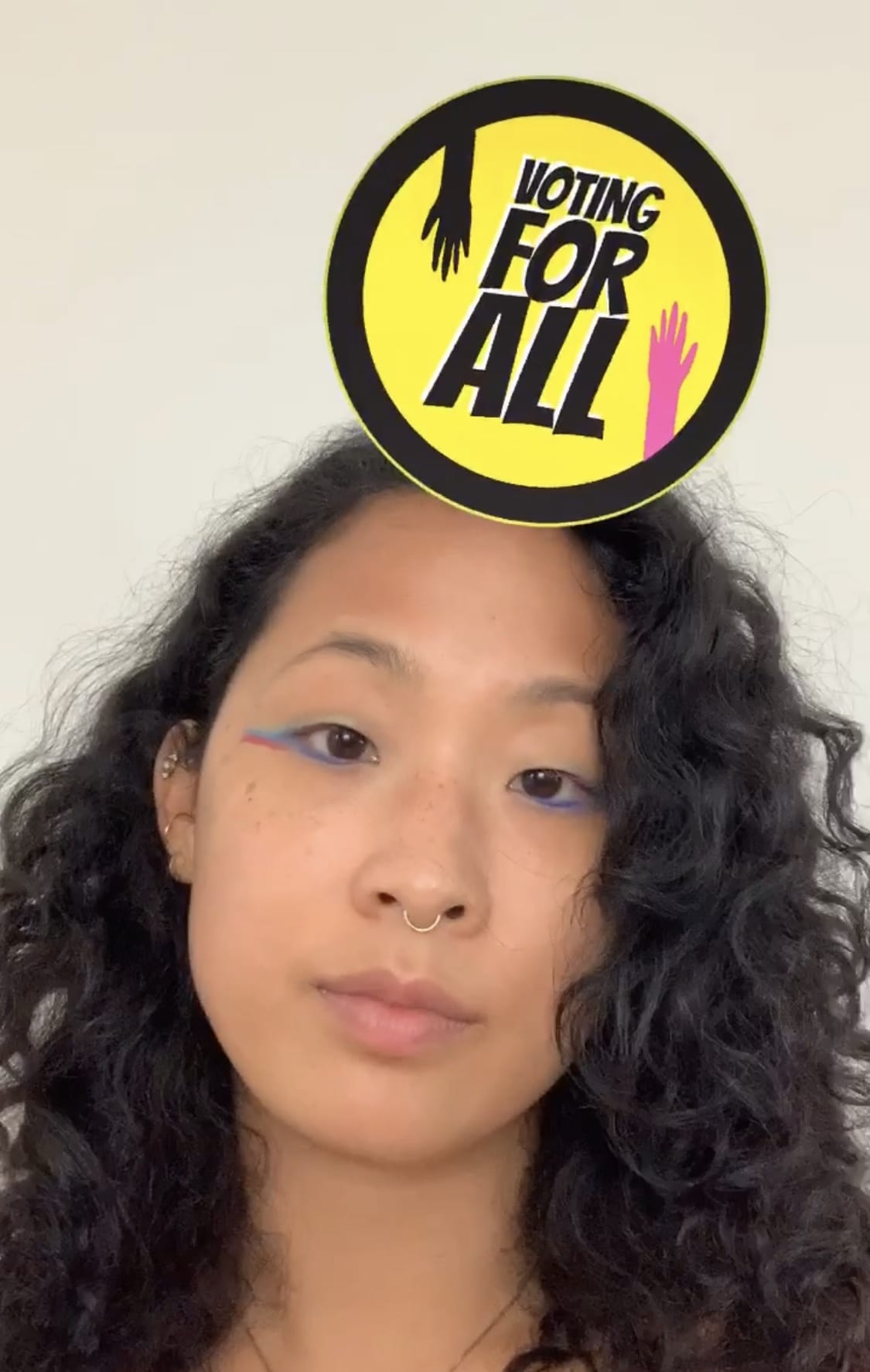 """Photo of artist Aram Han Sifuentes, wearing bright blue eyeliner and a nose ring, using an Instagram filter that places a sticker reading """"Voting for All"""" over her forehead"""