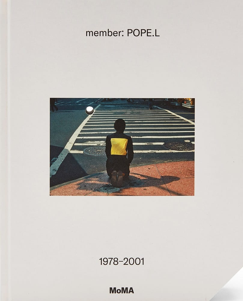 """Book cover for the exhibition catalog """"member: Pope.L."""" The cover is solid light-gray; at the center, a small color photo shows a man kneeling on the sidewalk in front of a crosswalk."""