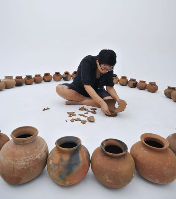 Color photograph of forty clay pots arranged in a circle. A woman dressed in black sits in the middle of the circle. In her left hand, she holds a broken clay pot.