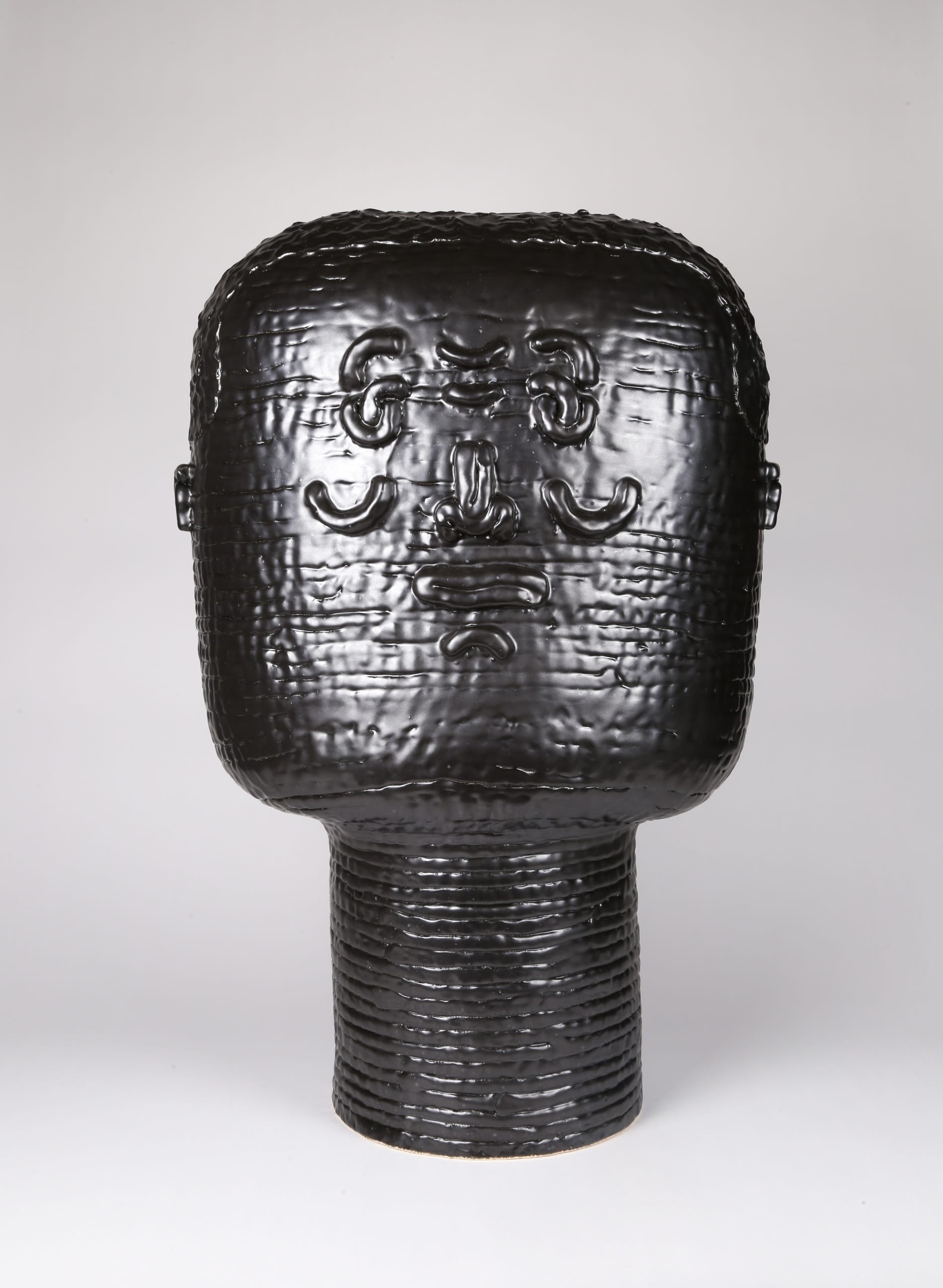 Color photograph with a frontal view of an abstract ceramic portrait head that appears to be made from a long coil of clay. The head is sculpted to appear square or block-like. The outlines of two eyes, a nose, a mouth, and two ears are affixed to its surface, and the figure seems to be expressing a shy grin. The object is monochromatic (black), with a slight sheen to the glaze.