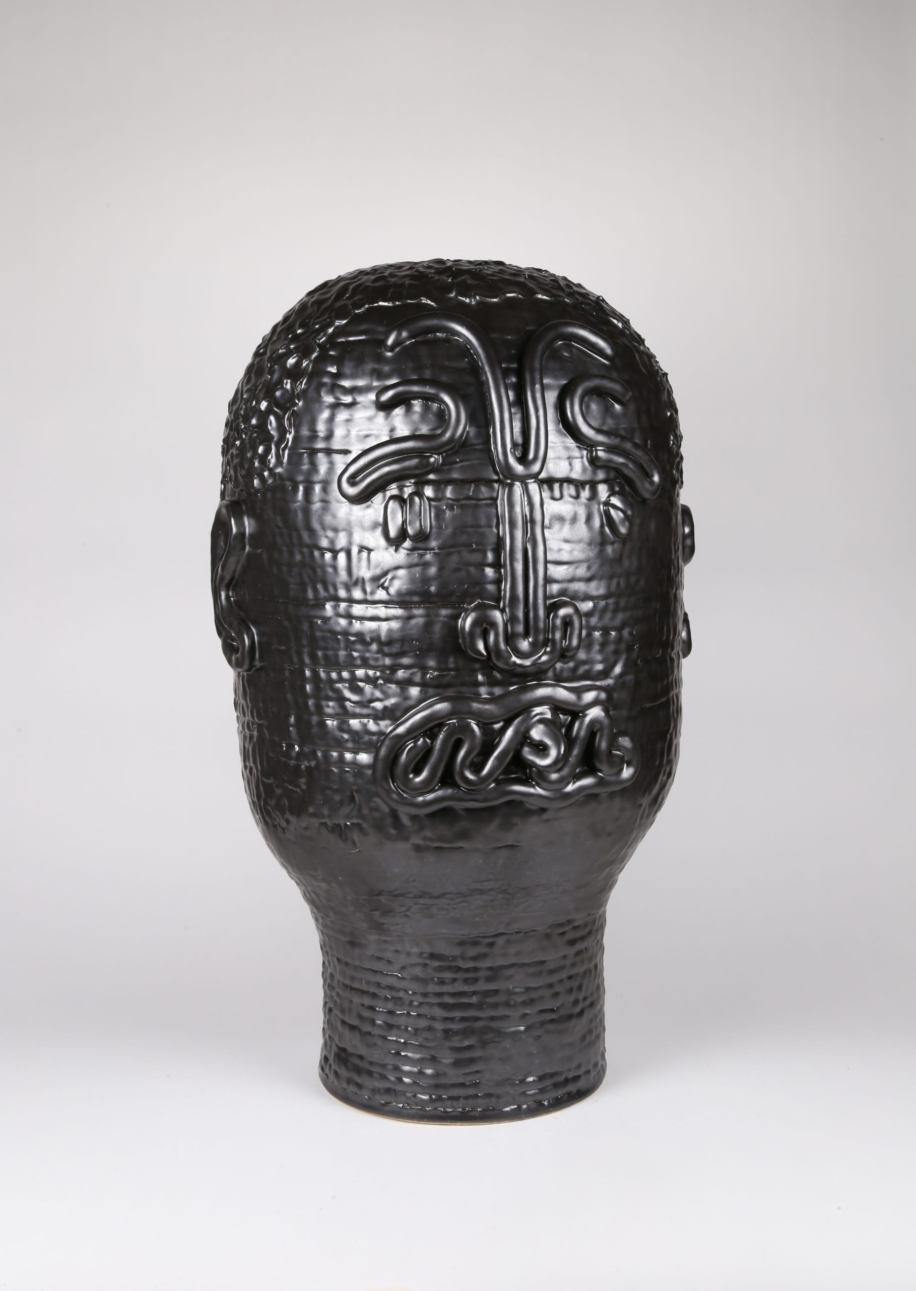 Color photograph with a frontal view of an abstract ceramic portrait head that appears to be made from a long coil of clay. The outlines of two eyes, a nose, a mouth, and two ears are affixed to its surface; the mouth appears tangled. The object is monochromatic (black), with a slight sheen to the glaze.