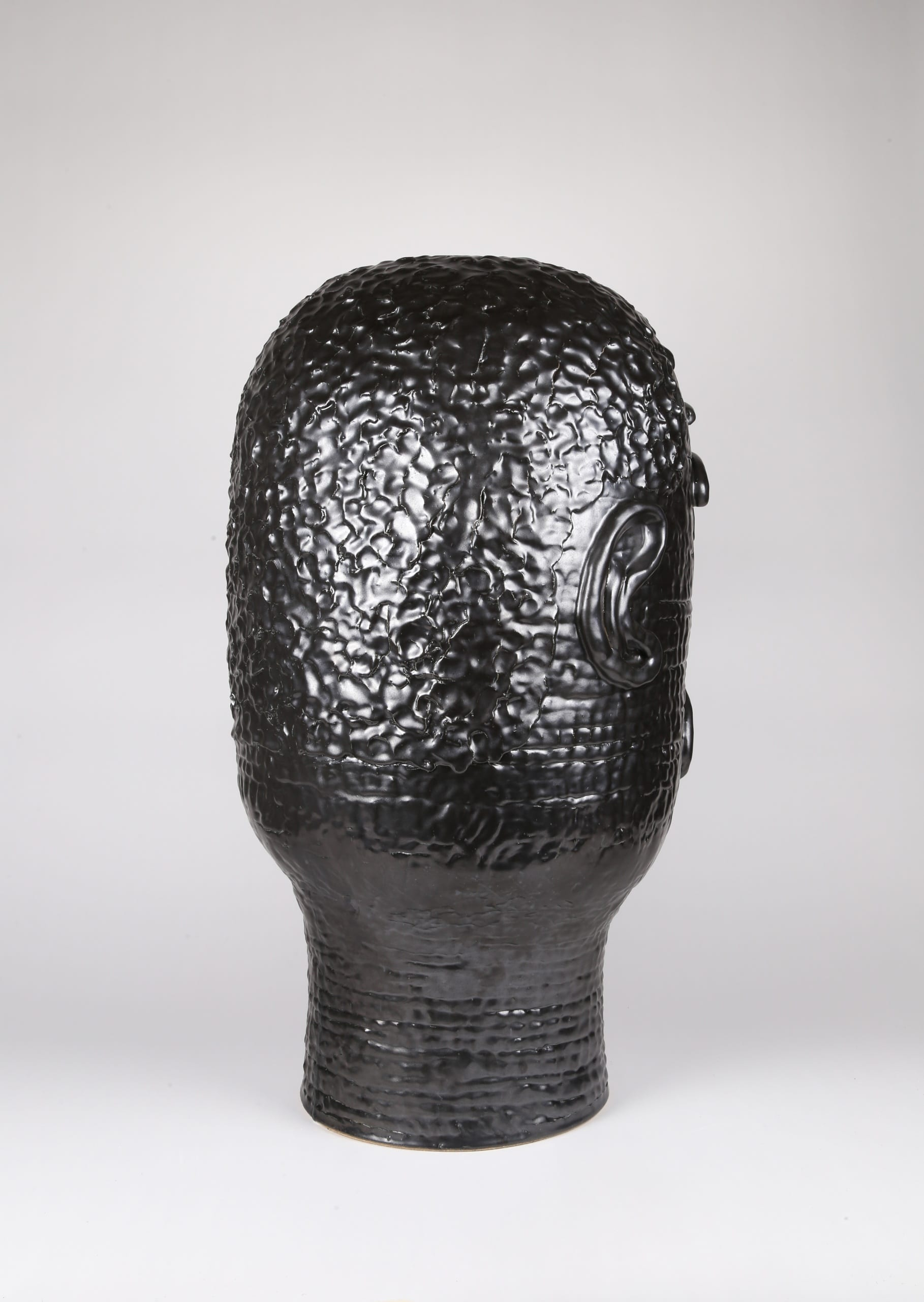 Color photograph with a back view of an abstract ceramic portrait head that appears to be made from a long coil of clay. The rear of the portrait details the texture of the figure's short cropped hair. The object is monochromatic (black), with a slight sheen to the glaze.