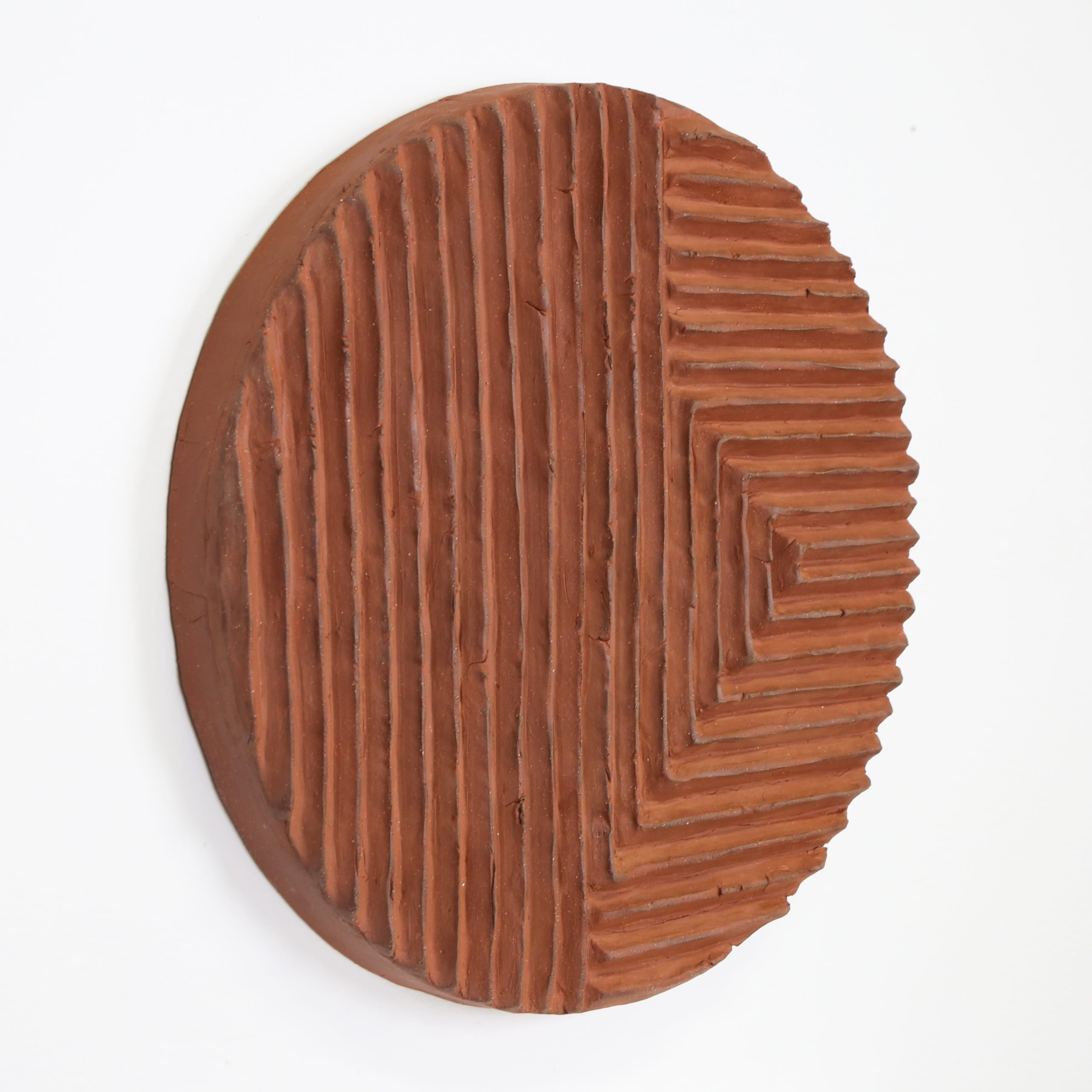 Color photograph with an oblique view of a terra-cotta disk with a series of raised, parallel lines sculpted onto its front, highlighting the texture of the clay and the depth of the ridges. The lines run up and down vertically on the left, and toward the object's right the lines are horizontal. The object appears to be unglazed.
