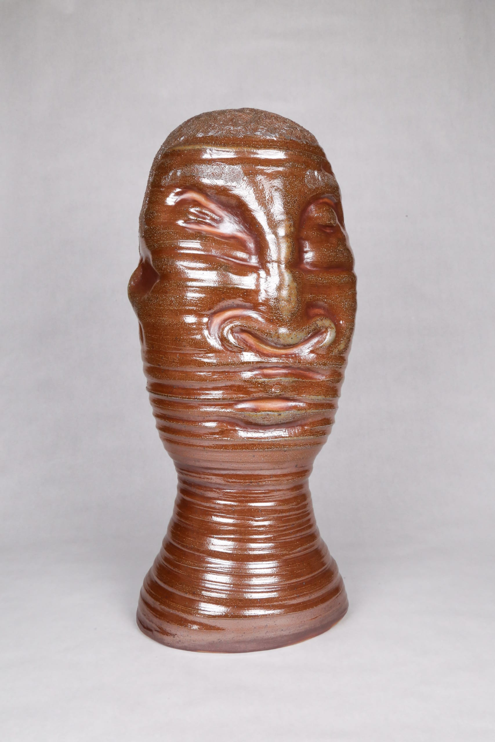Color photograph with a frontal view of an abstract ceramic portrait head, with distinctive ridges wrapping around the circumfrance of the head. The object is monochromatic (warm brown) with a light, luminescent glaze applied to its surface. It appears as though it was made on a spinning potter's wheel.