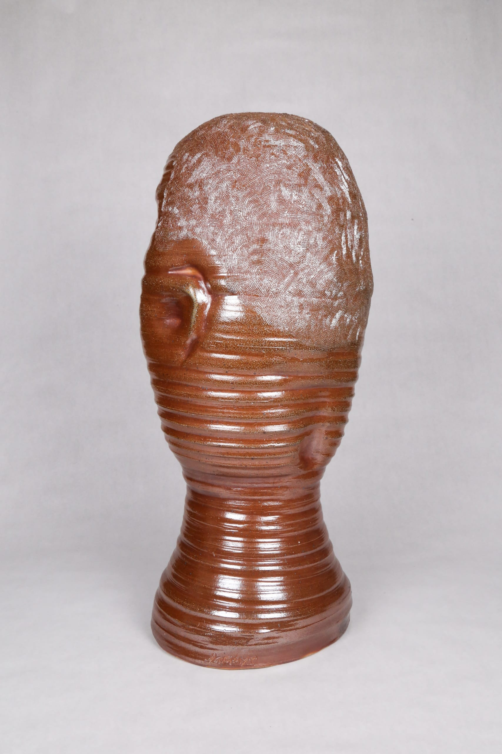 Color photograph with a back view of an abstract ceramic portrait head with distinctive ridges wrapping around the circumfrance of the head. The object is monochromatic (warm brown) with a light, luminescent glaze applied to its surface. It appears as though it was made on a spinning potter's wheel.