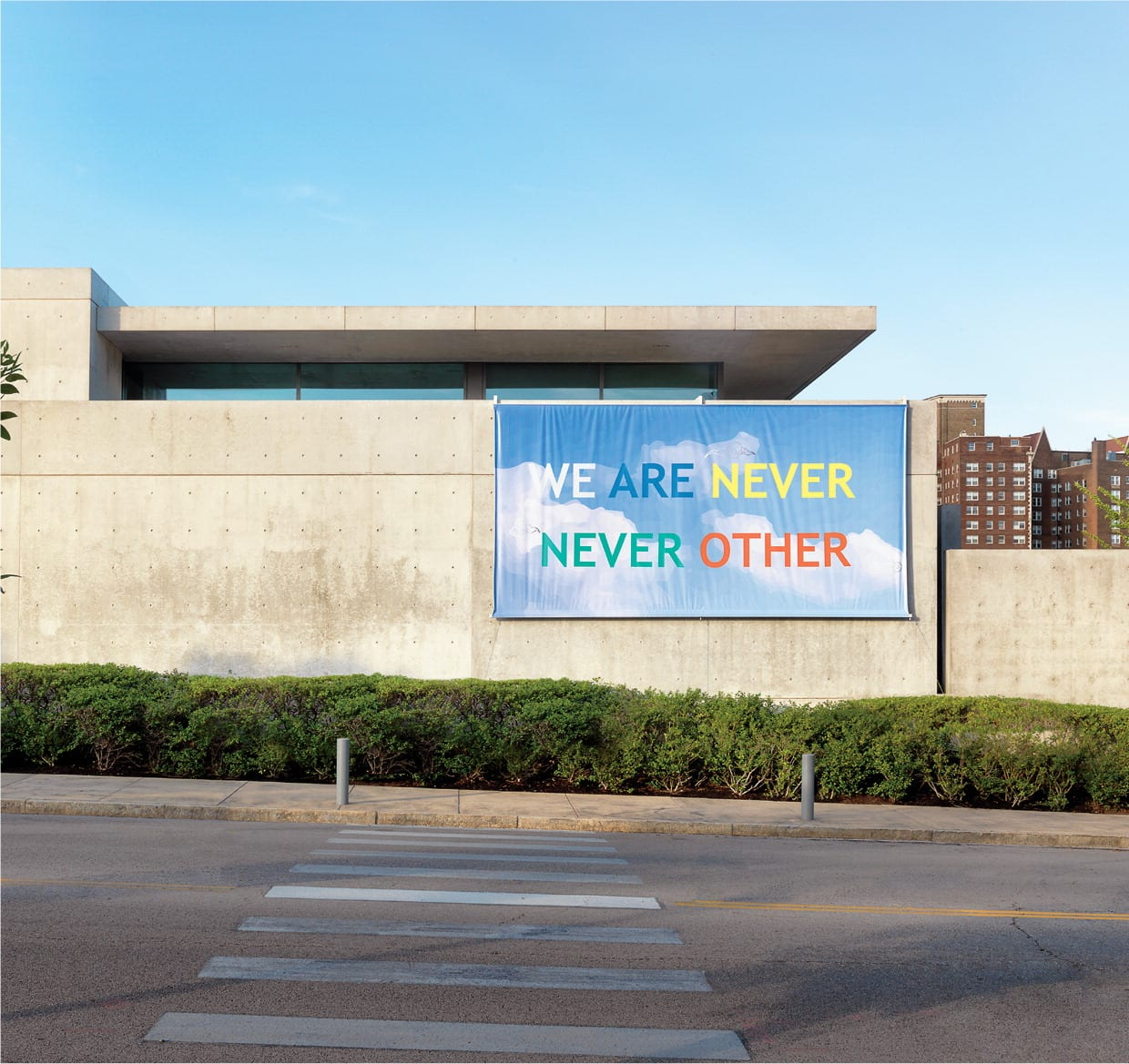 """A concrete building stands before clear blue sky. In front of the building are green bushes and a crosswalk on a street. On the wall of the building facing the camera, there is a large banner with a background of blue sky and clouds. In bold colorful letters over the image read the words, """"WE ARE NEVER NEVER OTHER."""""""