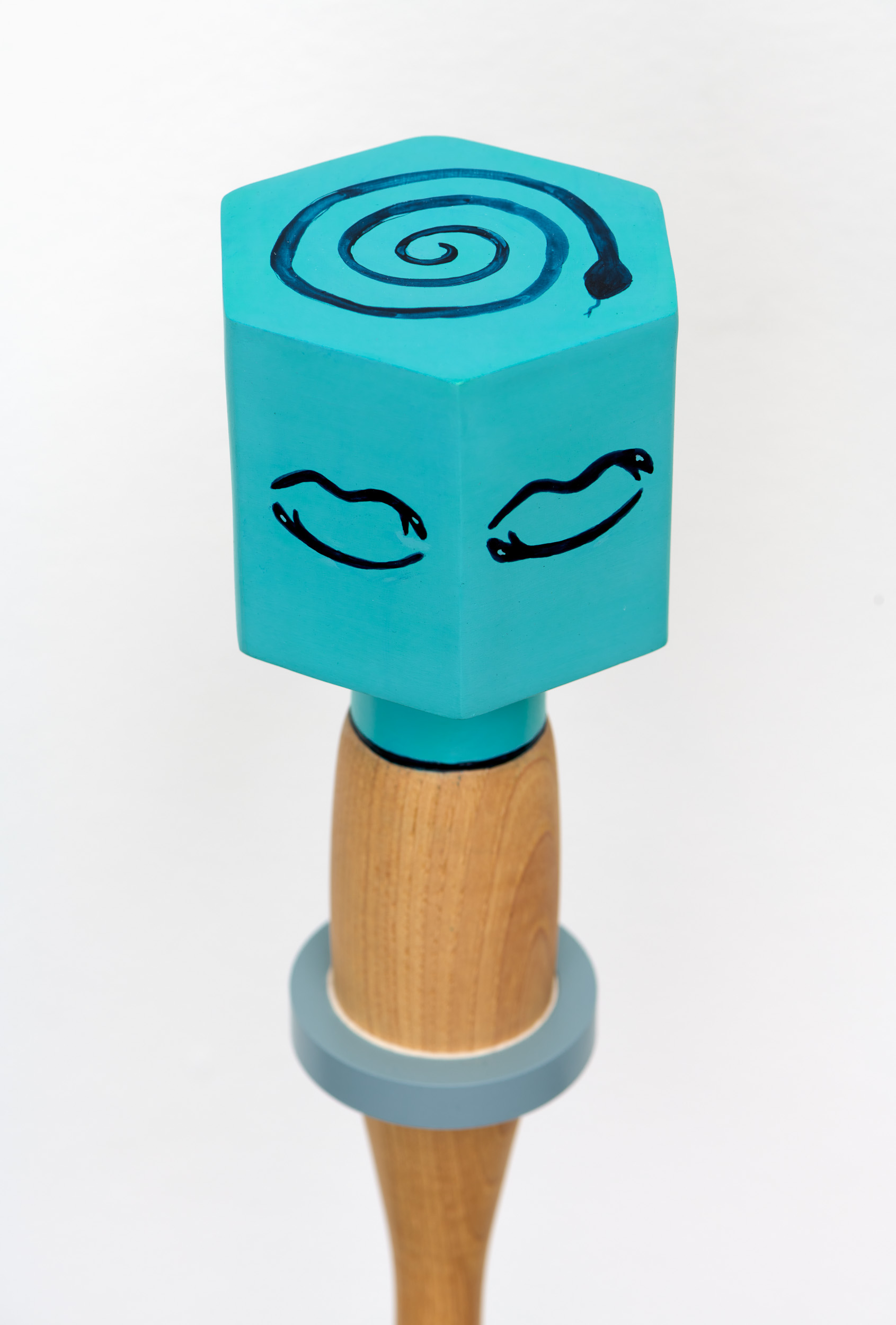 Detailed view of the top of a blue, hexagonal ceramic rattle with a wooden handle, revealing the image of a line drawing of a coiled snake on the top of the rattle.