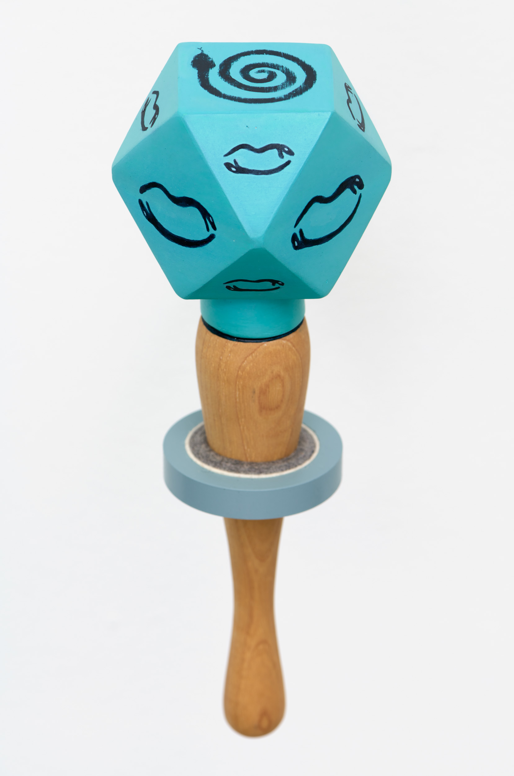 Detailed view of the top of a blue, multifaceted ceramic rattle with a wooden handle, revealing the image of a line drawing of a coiled snake on the top of the rattle.